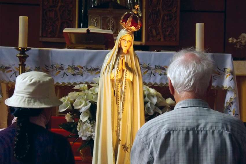 Parishioners pray before the Our Lady of Fatima statue at Canadian Martyrs Church in Toronto.