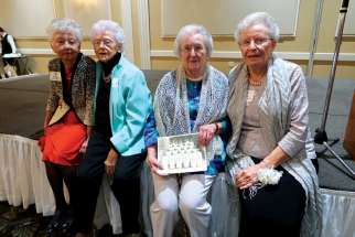 From left to right, Margaret Couch, Noreen O'Leary, Shirley Nach and Rose Simone pose with a picture of their graduation class of 1946.