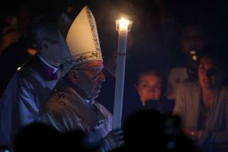 Pope Francis carries a candle as he arrives to celebrate the Easter Vigil in St. Peter's Basilica at the Vatican April 15.