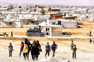 Syrian refugees walk at Zaatari refugee camp in the Jordanian city of Mafraq, near the border with Syria. Catholic Crosscultural Services has teamed with the federal government to try and link Syrian refugees with family and sponsors in Canada.