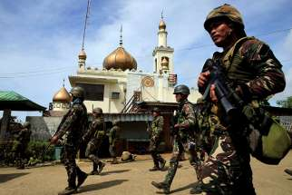 Philippine government soldiers walk past a mosque before their May 25 assault on Maute insurgents, who have taken over large parts of the town of Marawi. Catholic bishops in the region have expressed their support of the government's declaration of martial law, as long as it's temporary.