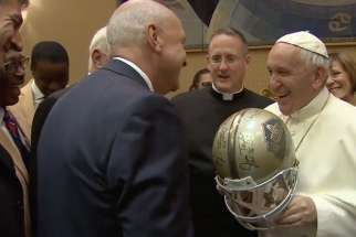 Pope Francis jokes with an NFL Hall of Fame representative about wearing a helmet that was a gift for the Pope during a visit at the Vatican on June 21, 2017.