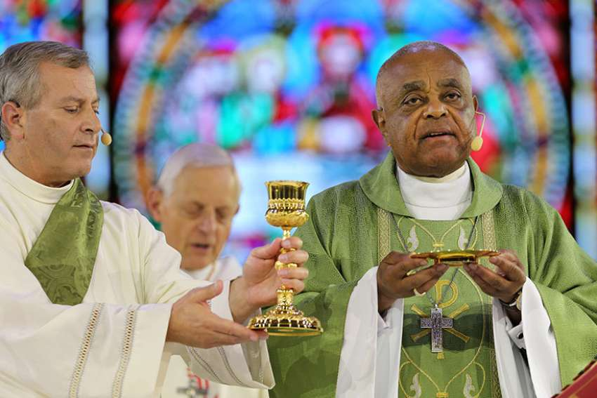 "Atlanta Archbishop Wilton D. Gregory, right, Concelebrates Mass during the ""Convocation of Catholic Leaders: The Joy of the Gospel in America"" July 2 in Orlando, Fla.  Bishops should look at ways to help verify and guarantee the validity and worthiness of the bread and wine used for the celebration of the Eucharist, the Vatican said in a recent document."