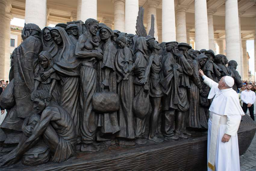 Pope Francis reaches out to the statue titled Angels Unawares by Canadian artist Timothy Schmalz at the Vatican last September. The statue depicts a group of migrants and refugees on a boat. Advocates are urging political leaders to include refugees and migrant workers in aid  support during the COVID-19 crisis.