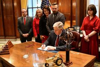 Missouri Gov. Mike Parson signs a bill into law banning abortion beginning in the eighth week of pregnancy, alongside state House and Senate members and pro-life coalition leaders at his office in Jefferson City May 24, 2019.