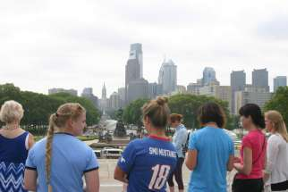 Women finish praying the rosary together at the top of the Philadelphia Museum of Art's iconic steps overlooking the Philadelphia skyline May 27. Pope Francis will have a similar view, including more than 1 million people, when he celebrates Mass in Philadelphia during his Sept. 22-27 visit to the United States.