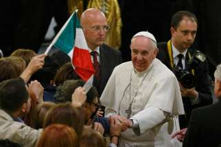 Italy's flag is seen as Pope Francis greets people at Rome's Church of St. Gregory VII March 21 after a prayer service for victims of the Mafia.