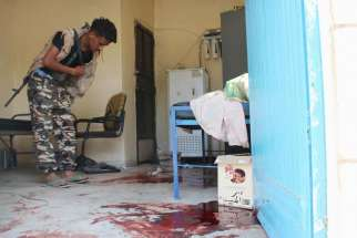 A pro-government militant inspects a room filled with blood after it was attacked by gunmen in Aden, Yemen, March 4.