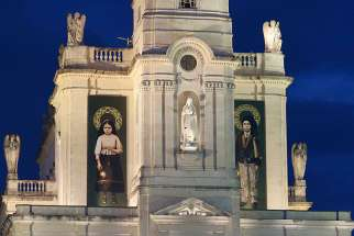 Banners showing Sts. Jacinta and Francisco Marto, two of the three Fatima seers, hang from the facade of the Basilica of Our Lady of the Rosary of Fatima as Pope Francis visits the Shrine of Our Lady of Fatima in Portugal, May 12.