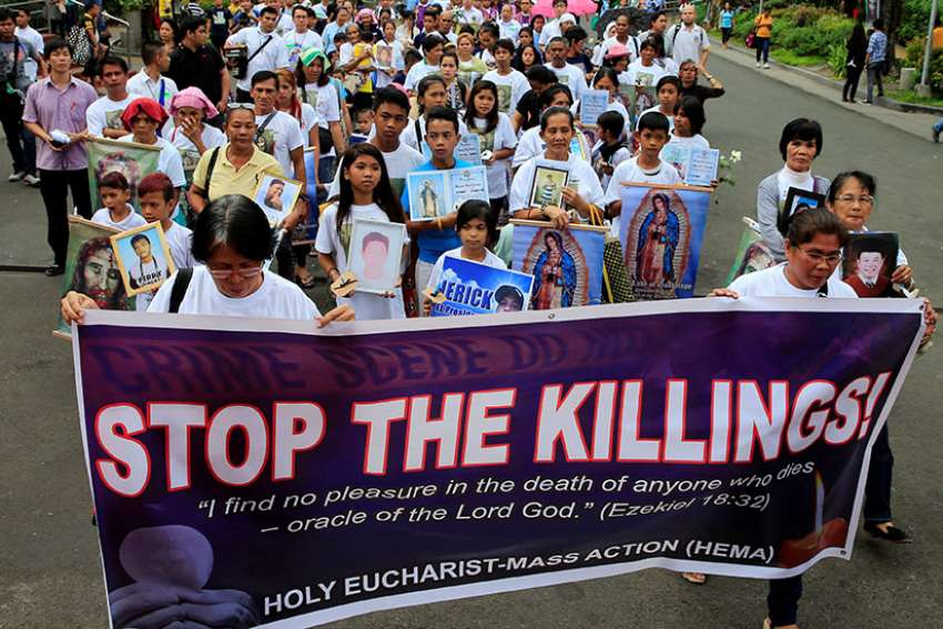 People hold images of Our Lady of Guadalupe and photos of their family members, who they say were killed because of their alleged involvement in illegal drugs, during a March 2 protest and march in memory of the victims in Manila, Philippines.