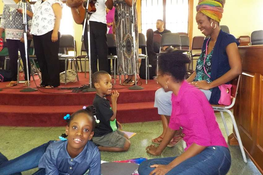 A volunteer, top right, looks on as a family with an autistic child left, attends Mass July 8 at Holy Trinity Church in Arouca, Trinidad.