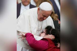 "Pope Francis embraces a woman as he greets disabled people during his general audience in St. Peter's Square at the Vatican April 9, 2014. In a letter marking the U.N.'s International Day of Persons with Disabilities Dec. 3, 2019, the pope said humanity needs to ""develop antibodies against a culture that considers some lives as class A and others as class B; this is a social sin!"""