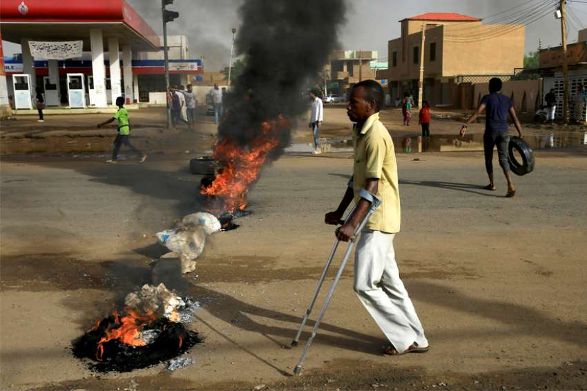 A man in Khartoum, Sudan, walks past a barricade June 3, 2019. Protesters there demand that the country's Transitional Military Council hand over power to civilians.