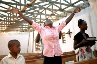 A woman prays in a roofless church in Torbeck, Haiti, Oct. 9 after Hurricane Matthew swept through the island nation.