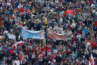 People hold banners during the canonizations of Sts. John XXIII and John Paul II at the Vatican April 27.
