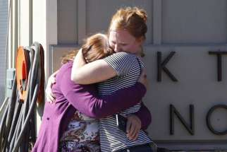 Umpqua Community College alumna Donice Smith, left, is embraced after learning one of her former teachers was killed in Roseburg, Ore., Oct. 1.