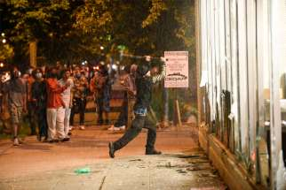 A protester in Minneapolis vandalizes an O'Reilly's near the Minneapolis Police Third Precinct May 27, 2020. Two days earlier George Floyd, an unarmed black man, was pinned down by a police officer kneeling on his neck before later dying in the hospital May 25.