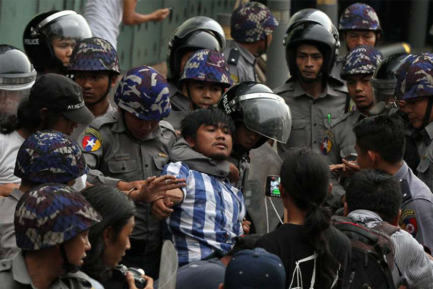 Police officers detain a student taking part in a rally demanding peace May 12 at the war-torn section of Yangon, Myanmar.