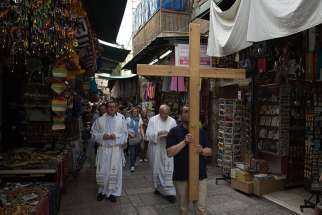 Catholic pilgrims walk past shops selling souvenirs May 20 on Via Dolorosa in Jerusalem's Old City. Many Holy Land residents say they are looking forward to Pope Francis' May 24-26 visit, despite inconveniences of crowds and traffic.