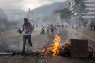 "A group of people protest during an opposition march April 22 in Caracas, Venezuela. In response to a renewed constitutional crisis in the country, the Venezuelan bishops' conference has called for ""peaceful civil disobedience"" to restore constitutional order."