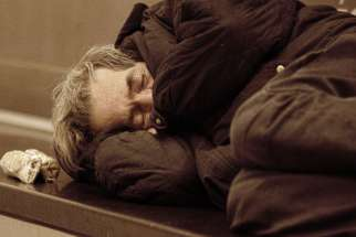 A homeless man sleeps in the street. Church on the Street is an outreach program that provides a listening presence for those who have felt life's hurts.