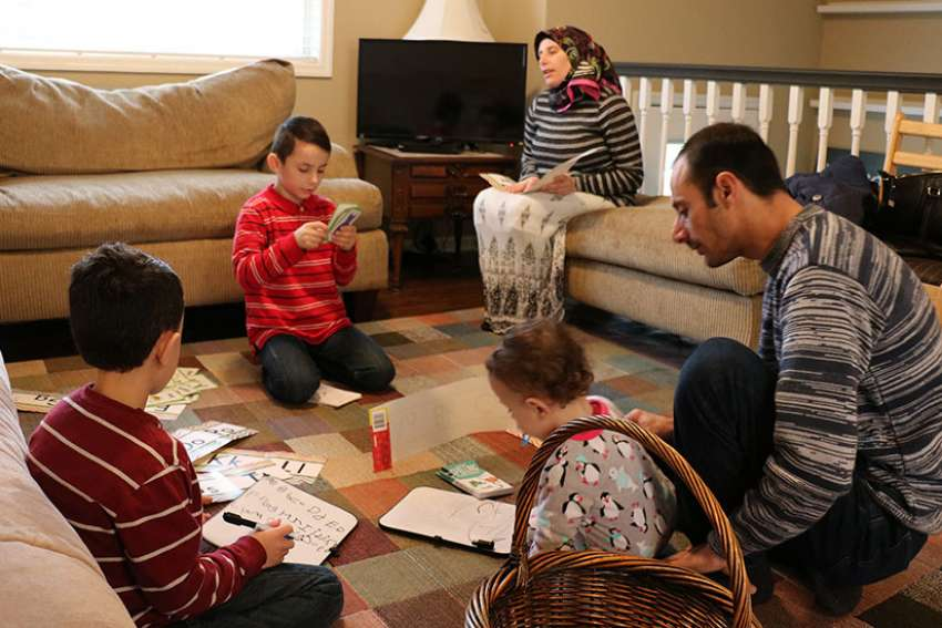 Syrian refugees Ahmed Al Kango and his wife, Sahar, help their children learn English Feb. 7 in their home in Elkhorn, Neb. Pictured from left, the children are Mohamad, Ghaith and Abdulrazzaq.