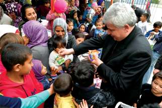 Cardinal Konrad Krajewski gives candy to children as he visits the Hope and Peace Center for refugees on the Greek island of Lesbos.