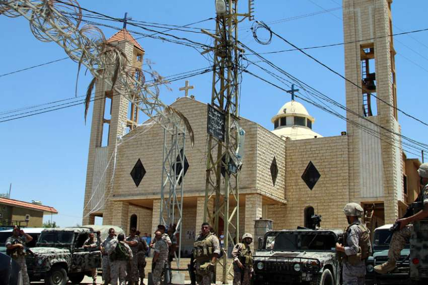 Lebanese army soldiers stand on an armored truck next to a church during a patrol after bombings in late June in Qaa. When a series of bombs exploded in the Lebanese Christian village near the Syrian border, it not only changed the lives of the victims and their families, but also the lives of Syrian refugees living nearby.