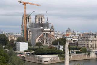 Workers remove scaffolding from the remains of the roof of the damaged Notre Dame Cathedral in Paris July 14, 2020, after the historic cathedral was partially destroyed in a 2019 fire. A new study has found that the amount of lead that settled to the ground and likely seeped into houses downwind of the fire was far greater than officials indicated at the time.