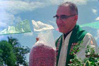 Archbishop Oscar Romero receives a sack of beans from parishioners following Mass outside of the church in San Antonio Los Ranchos in Chalatenango, El Salvador, in 1979. The Mass was held outdoors for fear of possible violence by the Salvadoran military. Before arriving at the church, the archbishop's delegation was detained by armed military for about 20 minutes.