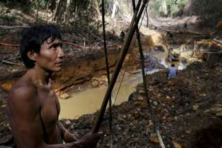 A Yanomami Indian stands near an illegal gold mine during a Brazilian government operation against illegal gold mining on indigenous land in the heart of the Amazon rainforest April 17, 2016.