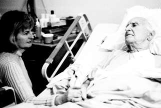 A Toronto woman praying with her 92-year-old father at Riverdale Hospital in 2004.