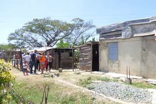 A group of people head toward an outdoor meeting space used by Catholics in the Cuban countryside in this early March photo. With few places to worship, some Catholics have been using makeshift chapels or mission houses, with little more than a tin roof over them, to pray, gather for Mass or teach the catechism in places where there is no parish.