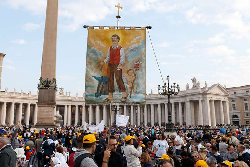 A man holds a banner showing new St. Nunzio Sulprizio during the canonization Mass for seven new saints celebrated by Pope Francis in St. Peter's Square at the Vatican Oct. 14. Among the new saints were St. Paul VI and St. Oscar Romero.