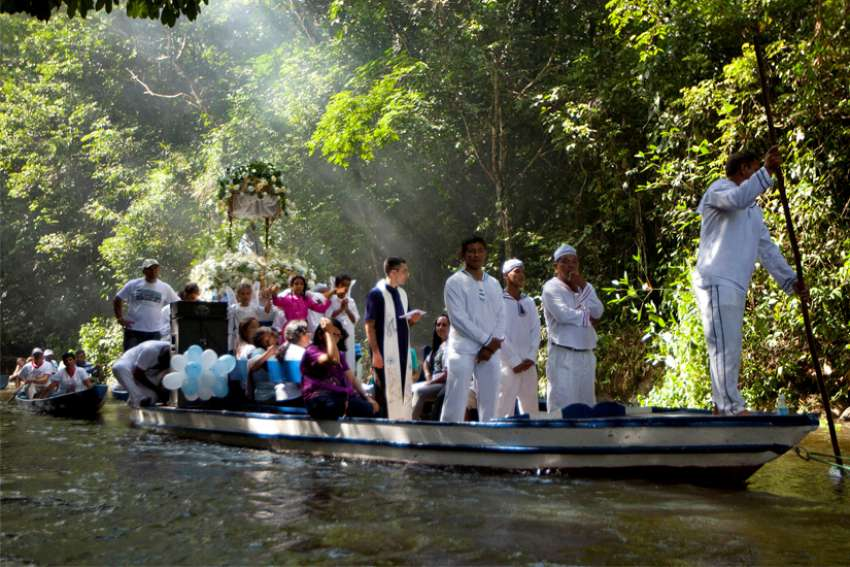 A priest holds a Bible as he leads pilgrims in prayer along during an annual river procession and pilgrimage on the Caraparu River in Santa Izabel do Para, Brazil, in this 2012 file photo.