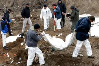 Forensic experts exhume bodies from a mass grave in Kozluk, Bosnia, in this Dec. 15, 2015, file photo.