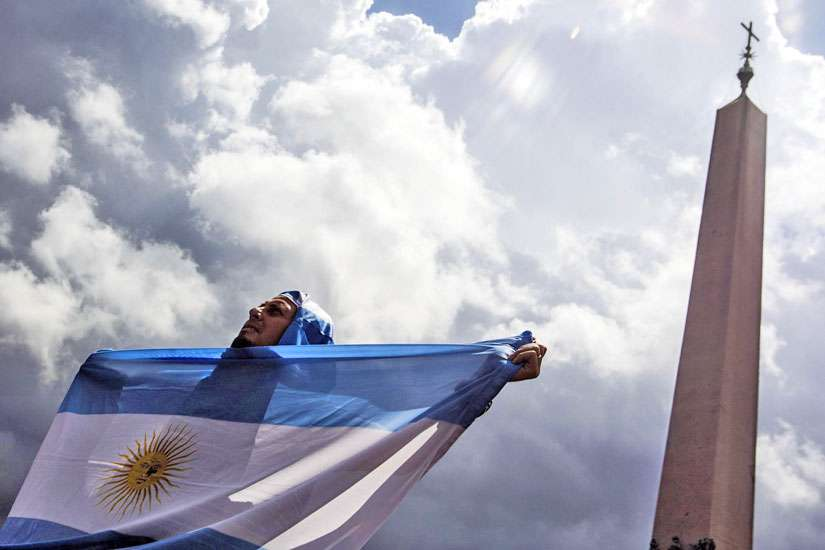 A man holds an Argentine flag at the Vatican in this July 13, 2014, file photo. The sainthood cause of Argentine Cardinal Eduardo Francisco Pironio, who organized the first World Youth Days as president of the Pontifical Council for the Laity, has been forwarded to the Vatican.