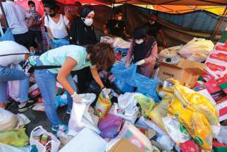 A volunteer gathers supplies in Beirut Aug. 5 to be distributed to people affected by the previous day's explosions.