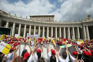 "Young people wave as Pope Francis leads the ""Regina Coeli"" from the window of his studio overlooking St. Peter's Square May 13 at the Vatican."