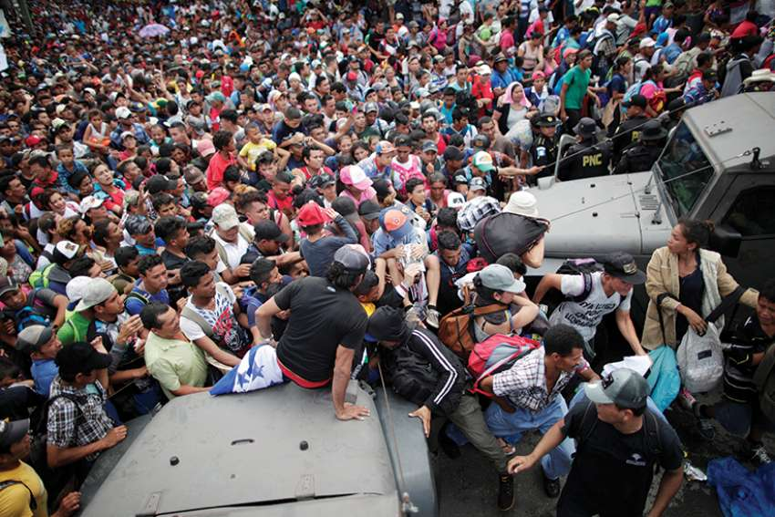 A large group of Honduran migrants, who are part of a caravan trying to reach the U.S., storm a border checkpoint in Tecun Uman, Guatemala, to cross into Mexico Oct. 19.