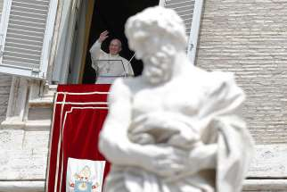 Pope Francis waves as he leads the Angelus from the window of his studio overlooking St. Peter's Square at the Vatican Aug. 2.
