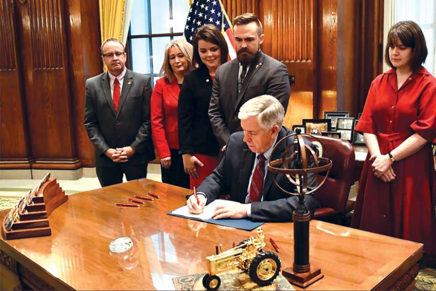 Missouri Gov. Mike Parson signs a bill banning abortion after the eighth week of pregnancy, alongside other legislators and pro-life leaders. Archbishop Joseph F. Naumann of Kansas City praised states for passing pro-life legislation in recent months.