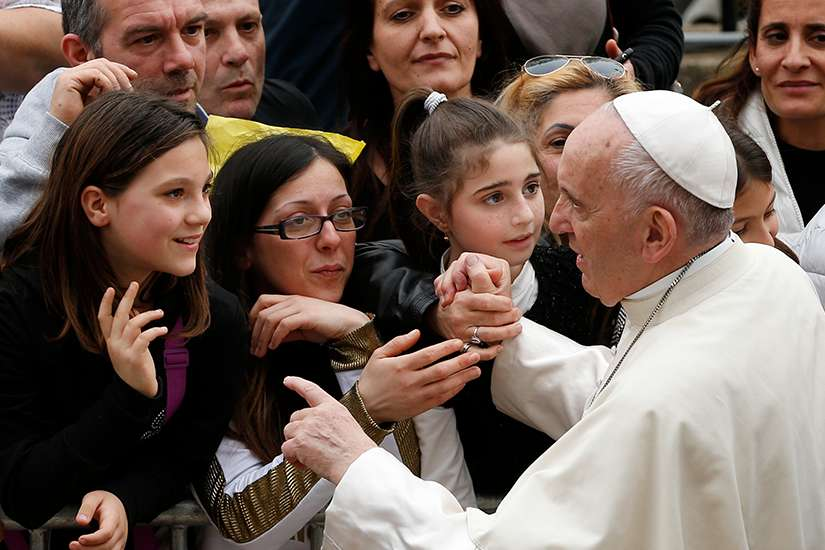 Pope Francis greets people as he visits St. Paul of the Cross Parish in Rome April 15.