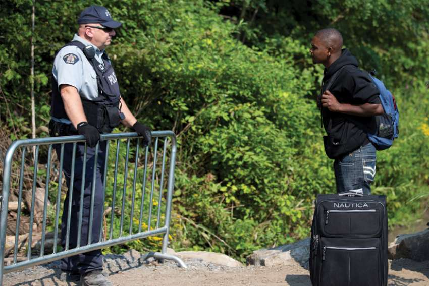 A Haitian man talks with a Royal Canadian Mounted Police officer as he waits to cross the U.S.-Canada border into Quebec in 2017.
