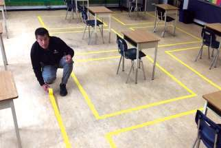 Tape is placed on the floors of St. Helen's Elementary School in Burnaby, B.C., marking where students will sit to maintain physical distancing.