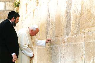 Rabbi Michael Melchior watches as Pope John Paul II prays at Judiasm's holiest site, the Western Wall, in Jerusalem in March 2000.