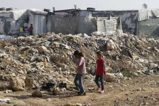 Syrian girls walk near garbage inside an informal refugee camp in Zahle, Lebanon.
