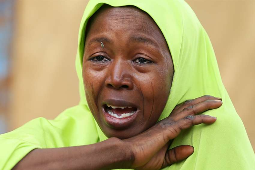 A relative of one of the missing Nigerian school girls reacts Feb. 23 in Dapchi, Yobe State, after an attack on the village by suspected Boko Haram insurgents. A Nigerian bishop has appealed to the government to work for the rescue of the 110 girls of the Government Girls Science and Technical College.