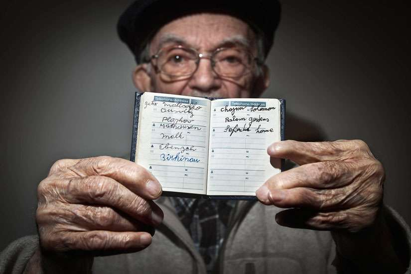 Holocaust survivor Hy Abrams, 90, poses for a portrait Jan. 15 in the Brooklyn borough of New York with a book that documents all the different concentration camps he was held in during World War II. Abrams was taken at age 20 by German Nazi soldiers an d separated from his mother, father, brother and three sisters.