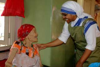 A woman smiles as she is greeted by Sister Marica of the Missionaries of Charity at a home for the elderly in the Pashupatinath temple in Kathmandu, Nepal, July 4.